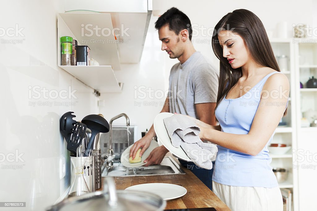 Couple at home washing dishes. stock photo