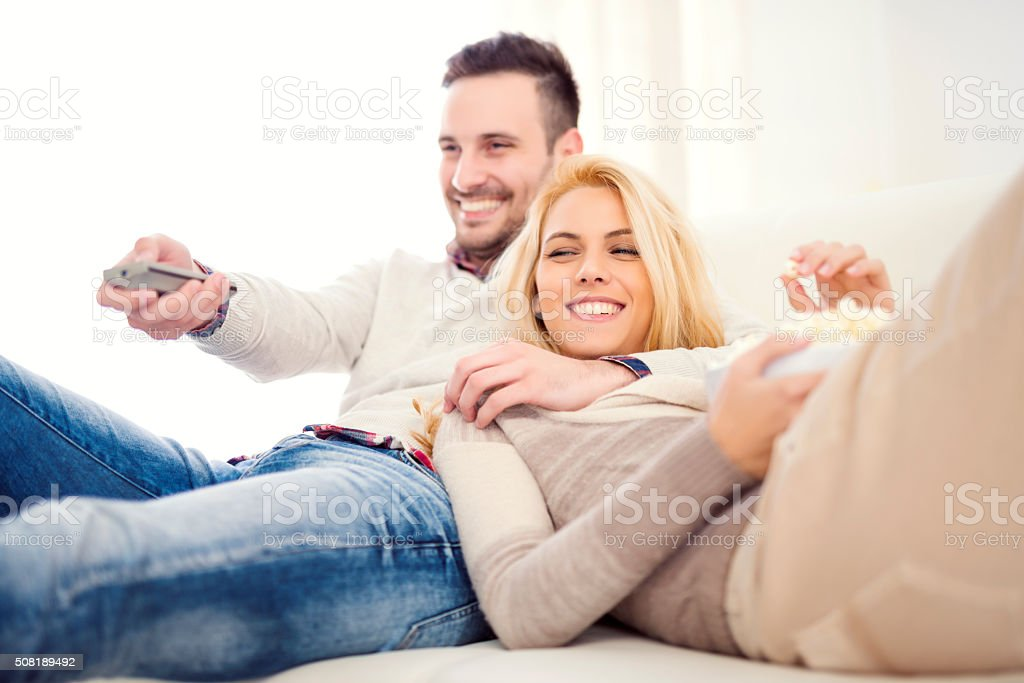 Couple at home watching TV stock photo