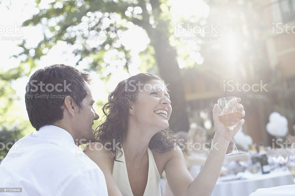 Couple at outdoor party with white wine laughing royalty-free stock photo