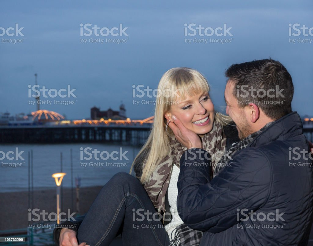 Couple at seaside in winter looking into eyes stock photo