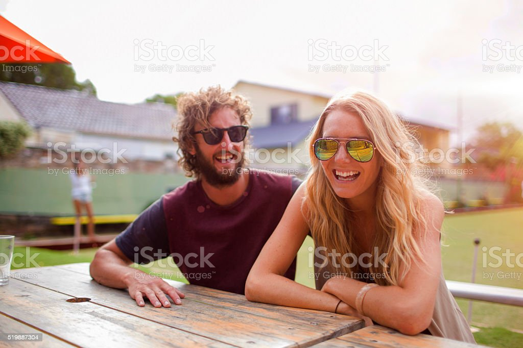 Couple at table laughing at lawn bowls club Australia stock photo