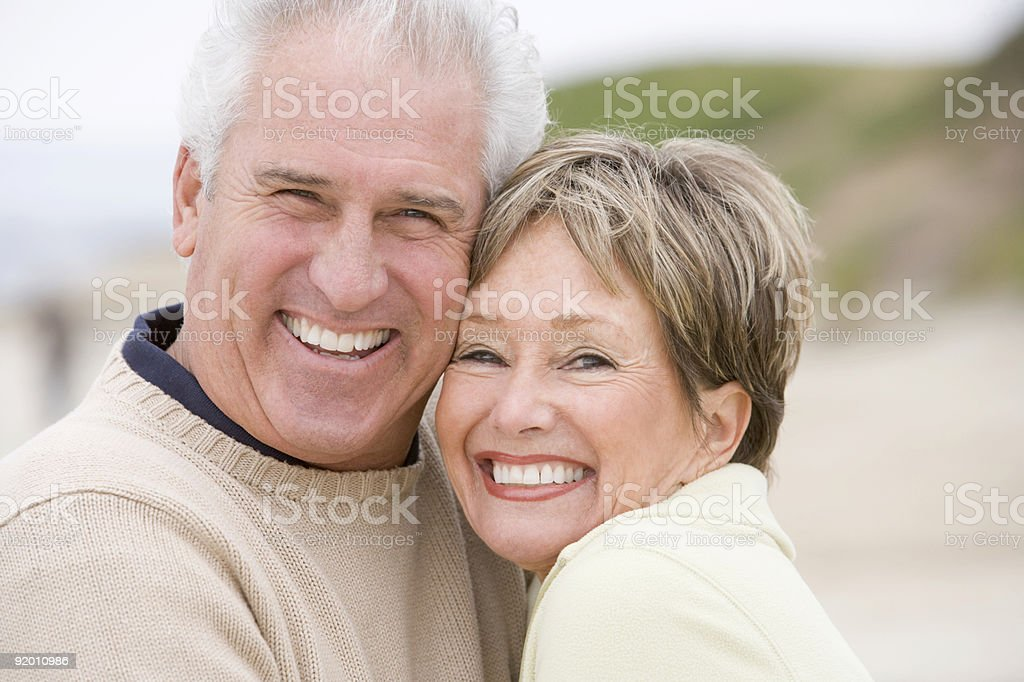 Couple at the beach smiling stock photo