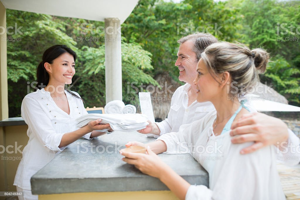 Couple at the front desk of a hotel stock photo