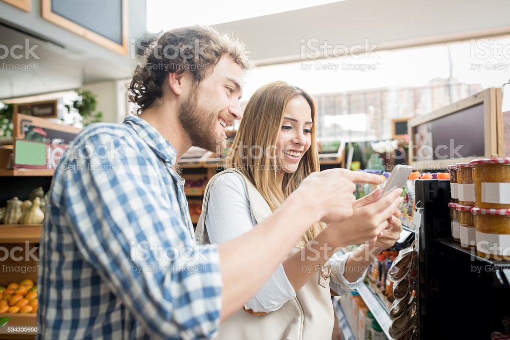 Couple at the grocery store going through a shopping list stock photo