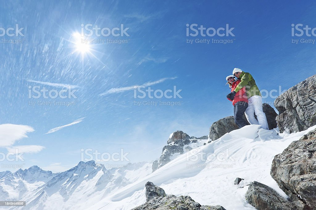Couple at the top of a  blizzard snowy mountain stock photo