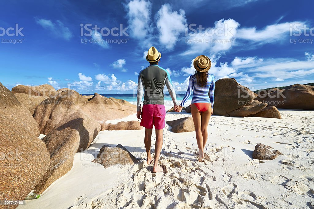 Couple at tropical beach wearing rash guard stock photo