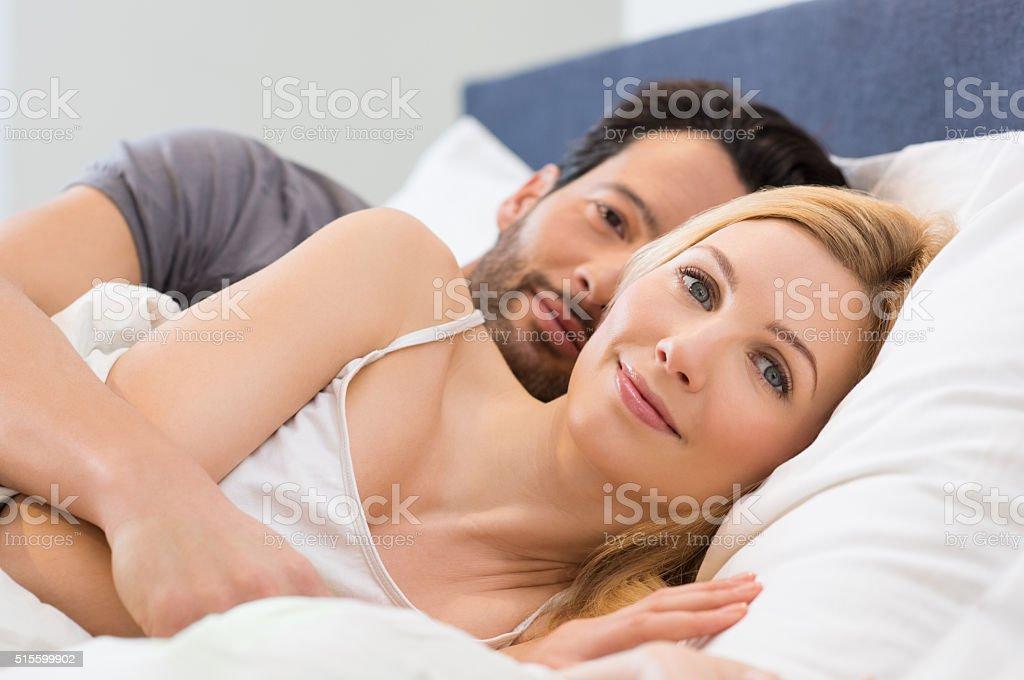 Couple awake on bed stock photo