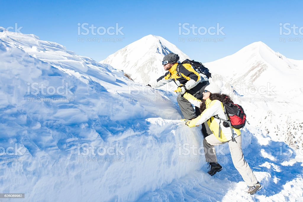 Side view of young couple backpackers holding hands and moving up in...