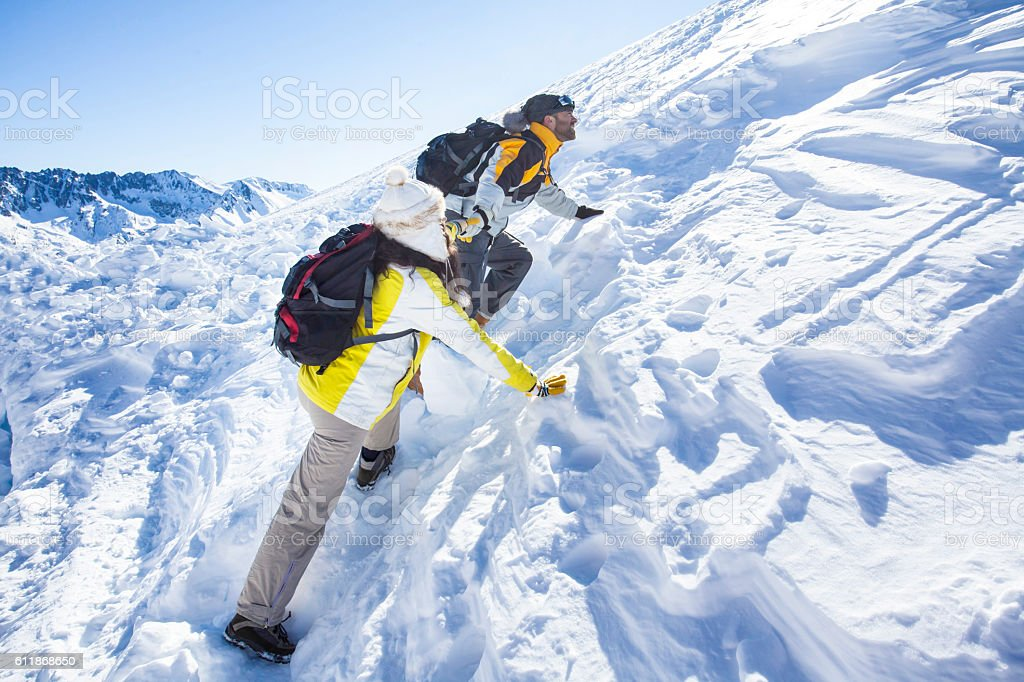 Side view of young couple backpackers moving up in the snow mountain....