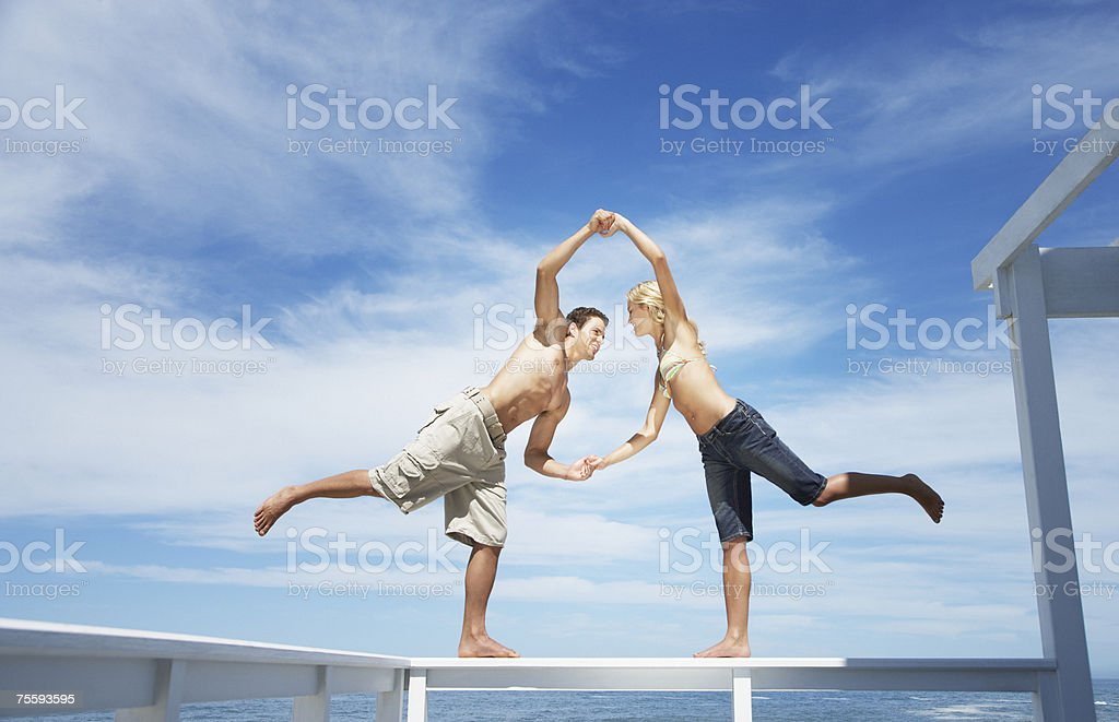 A couple balancing on the rail of a terrace royalty-free stock photo