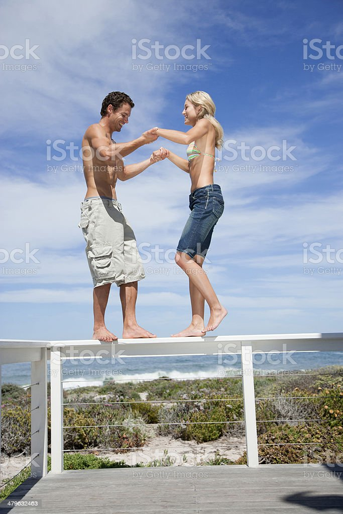 A couple balancing on the rail of a terrace with holding hands stock photo