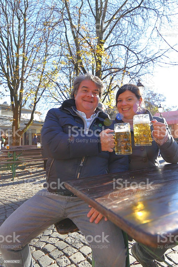 Couple Beer Cheers at Beergarden in Munich Viktualienmarkt stock photo