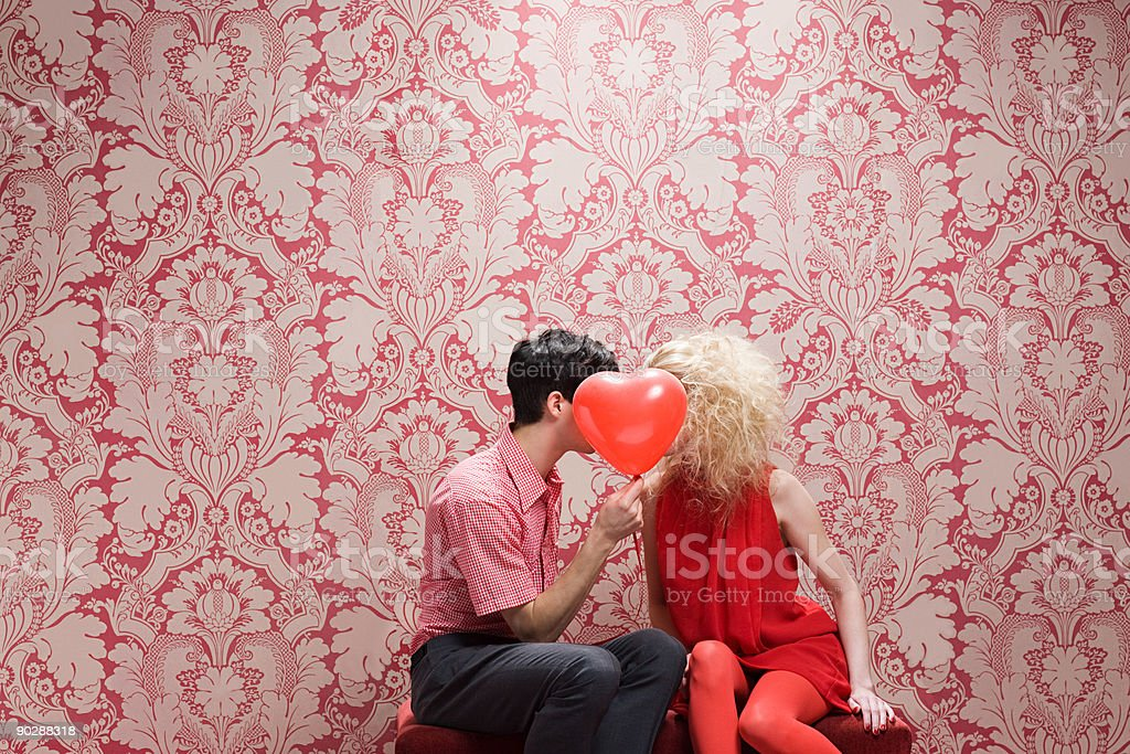Couple behind heart shaped balloon stock photo