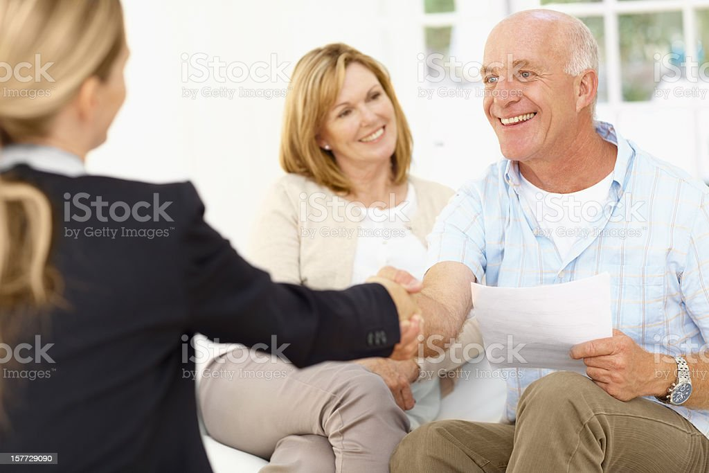 Couple being congratulated after signing paperwork royalty-free stock photo