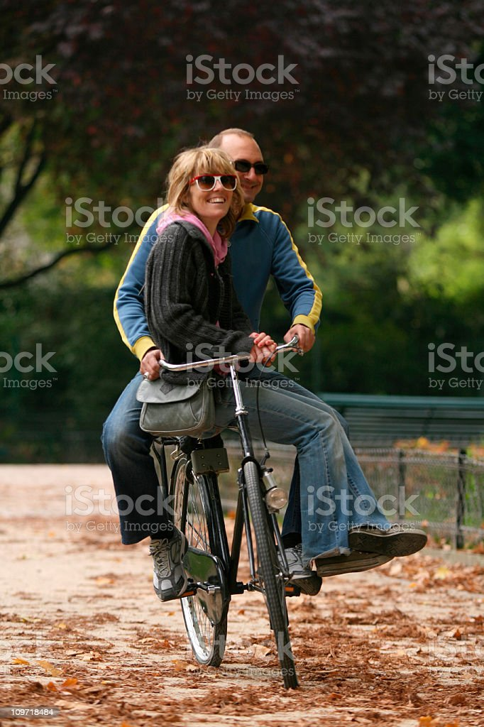 Couple Bicycling on Same Bike Through Park royalty-free stock photo