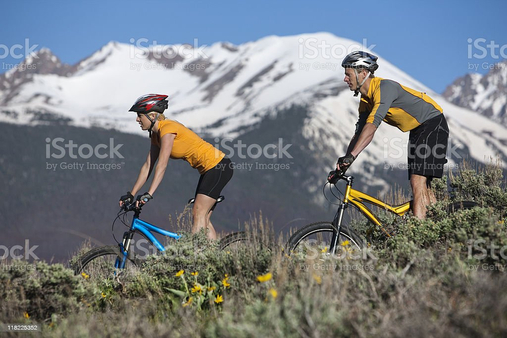 Couple Bicycling With Rocky Mountains In  Background royalty-free stock photo