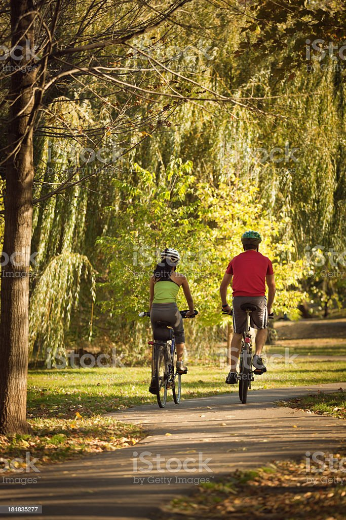 Couple Bicyclists Biking in Autumn Park Bike Path for Exercise royalty-free stock photo