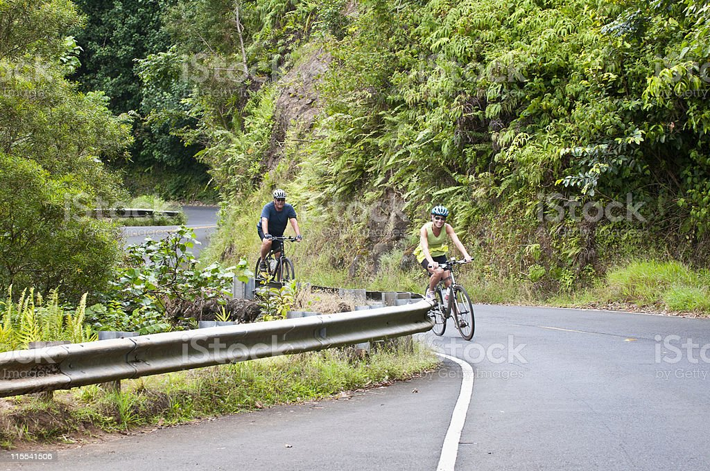 Couple biking down winding road in Hana, Maui royalty-free stock photo