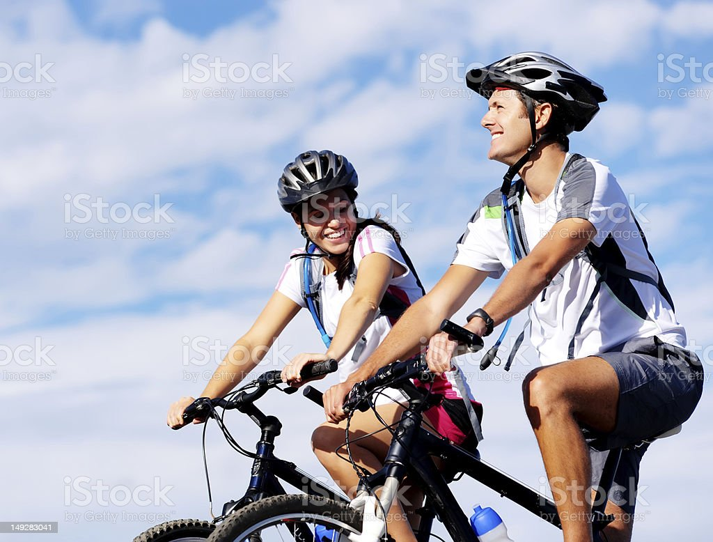 Couple biking together wearing helmets stock photo