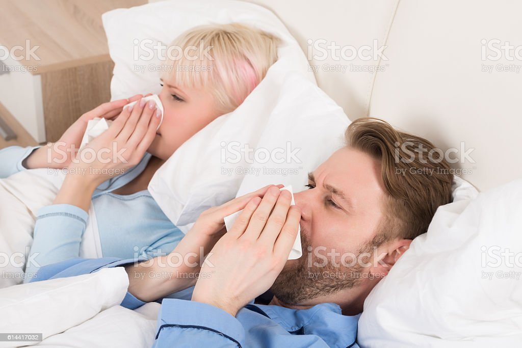 Couple Blowing Their Nose While Lying In Bed stock photo
