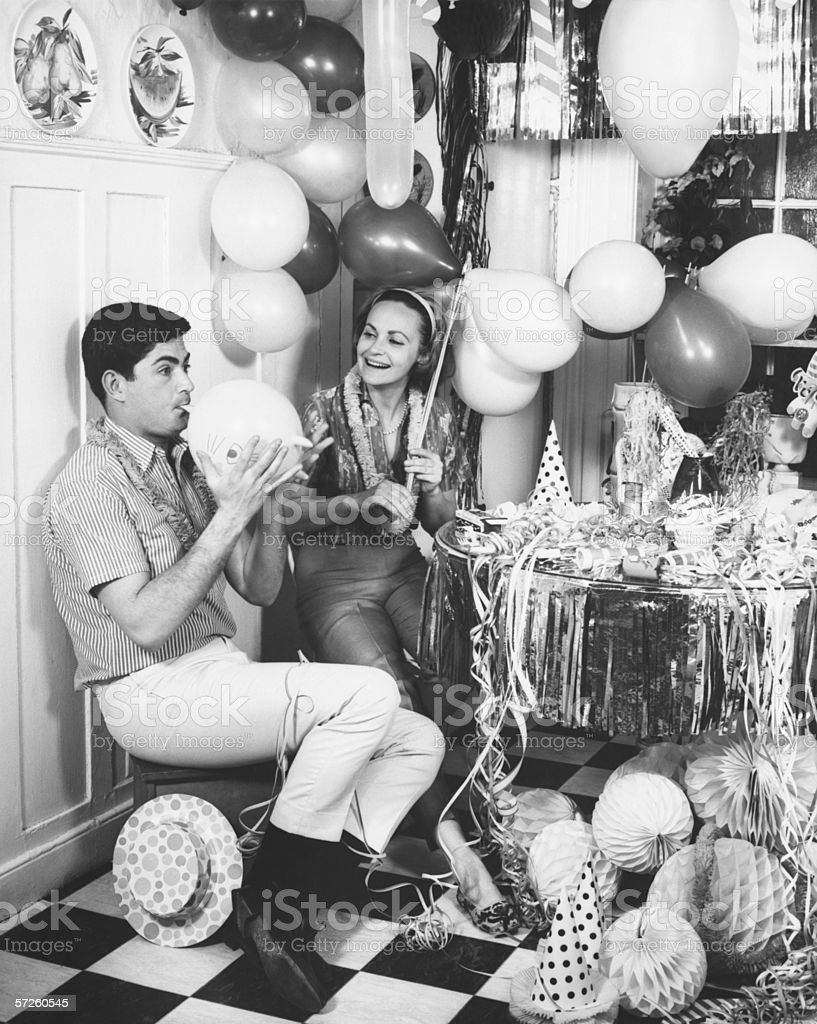Couple blowing up balloons in kitchen for party, (B&W) royalty-free stock photo