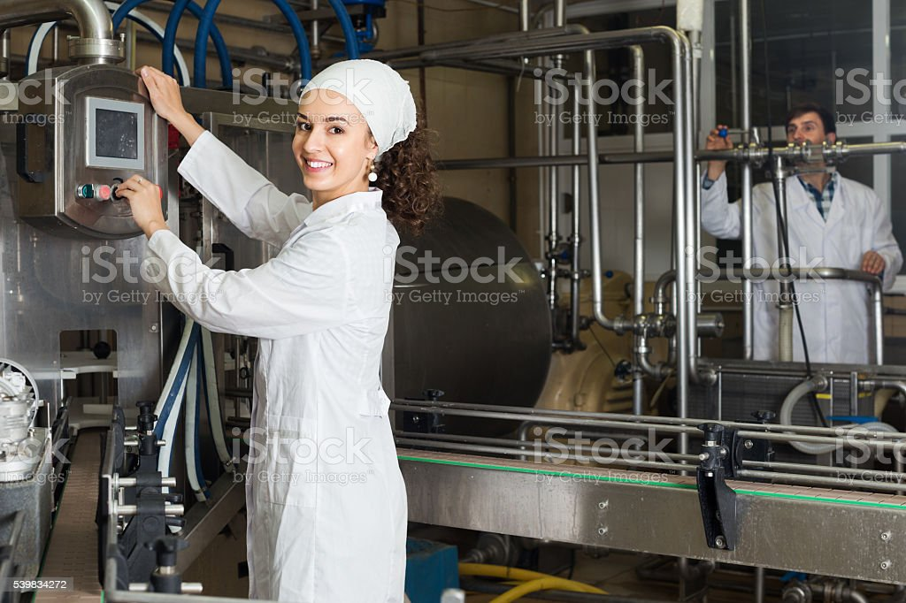Couple bottling milk on manufacture stock photo