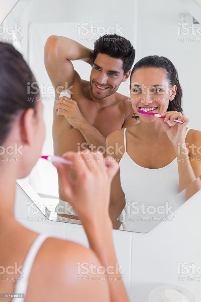 Couple brush teeth and apply deodorant in front of mirror stock photo