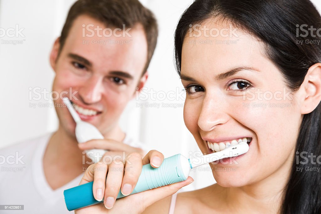 A couple brushing their teeth with electric toothbrushes royalty-free stock photo