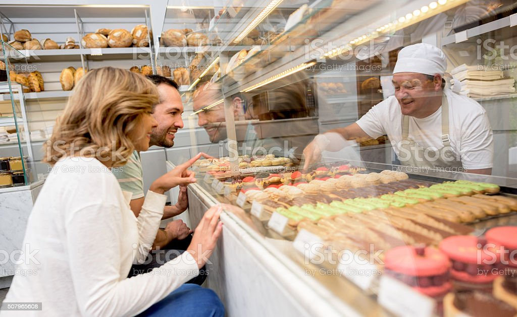 Couple buying a dessert at a pastry shop stock photo