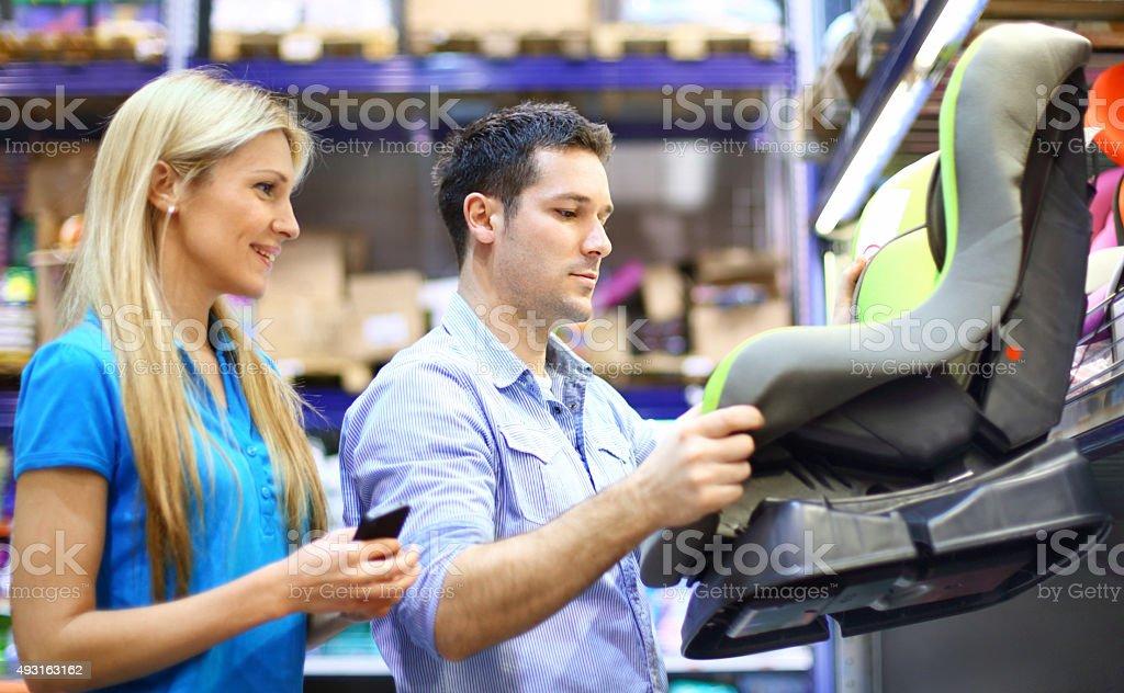 Couple buying baby car seat. stock photo