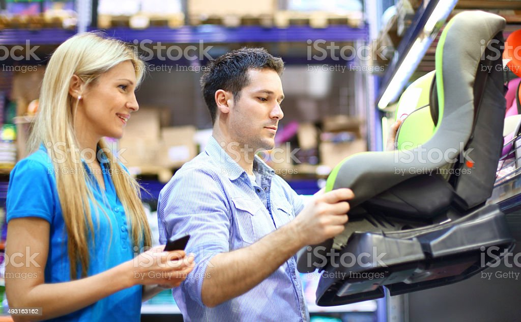 Couple buying baby car seat. stock photo