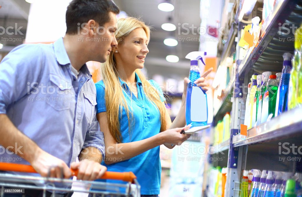 Couple buying cleaning liquid in supermarket. stock photo