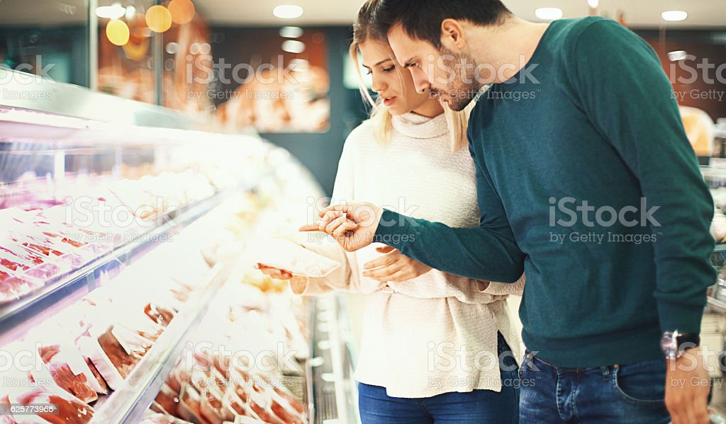 Couple buying fresh meat in supermarket. stock photo