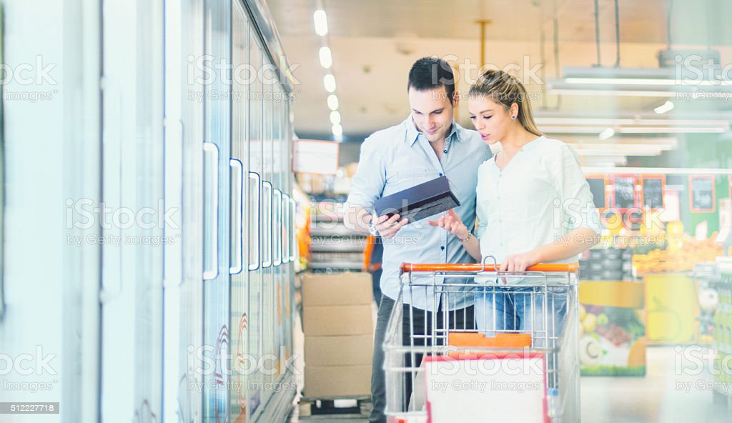 Couple buying frozen food in supermarket. stock photo