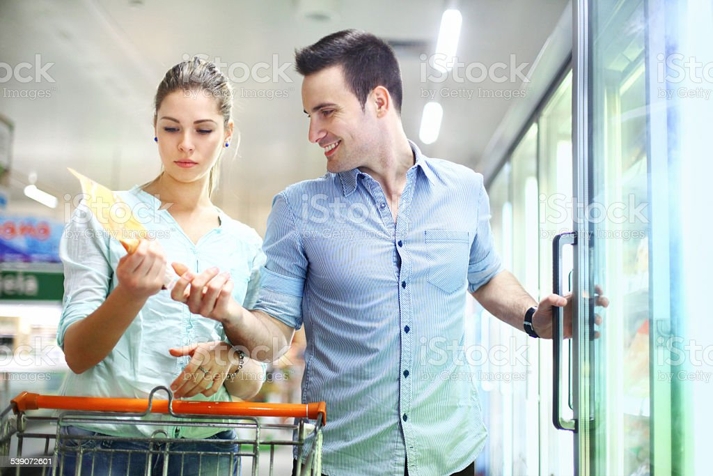 Couple buying frozen food in supermarket. stock photo
