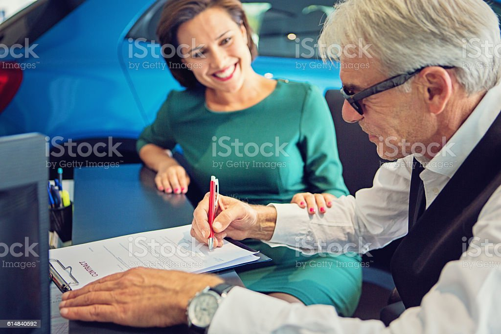 Couple buying new car and signing the contract stock photo