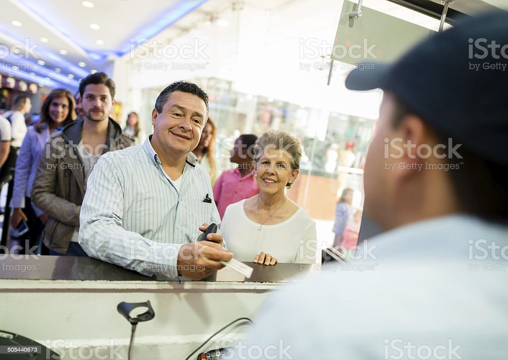 Couple buying tickets at the movies stock photo
