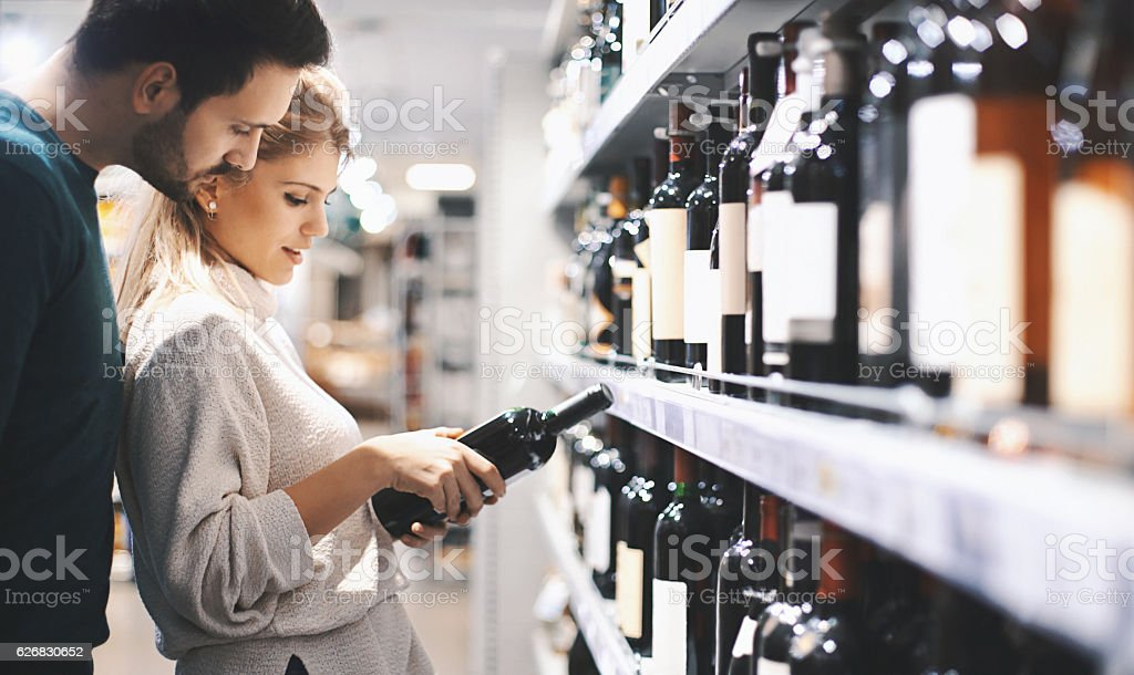 Couple buying wine in supermarket. stock photo