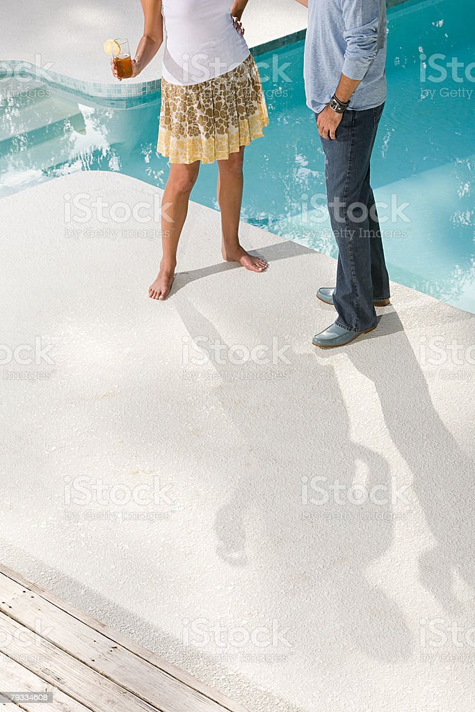 Couple by swimming pool stock photo