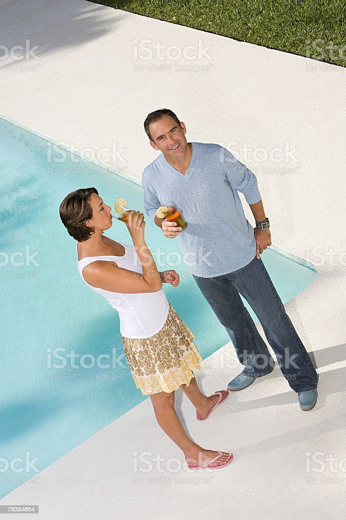 Couple by swimming pool with drinks stock photo
