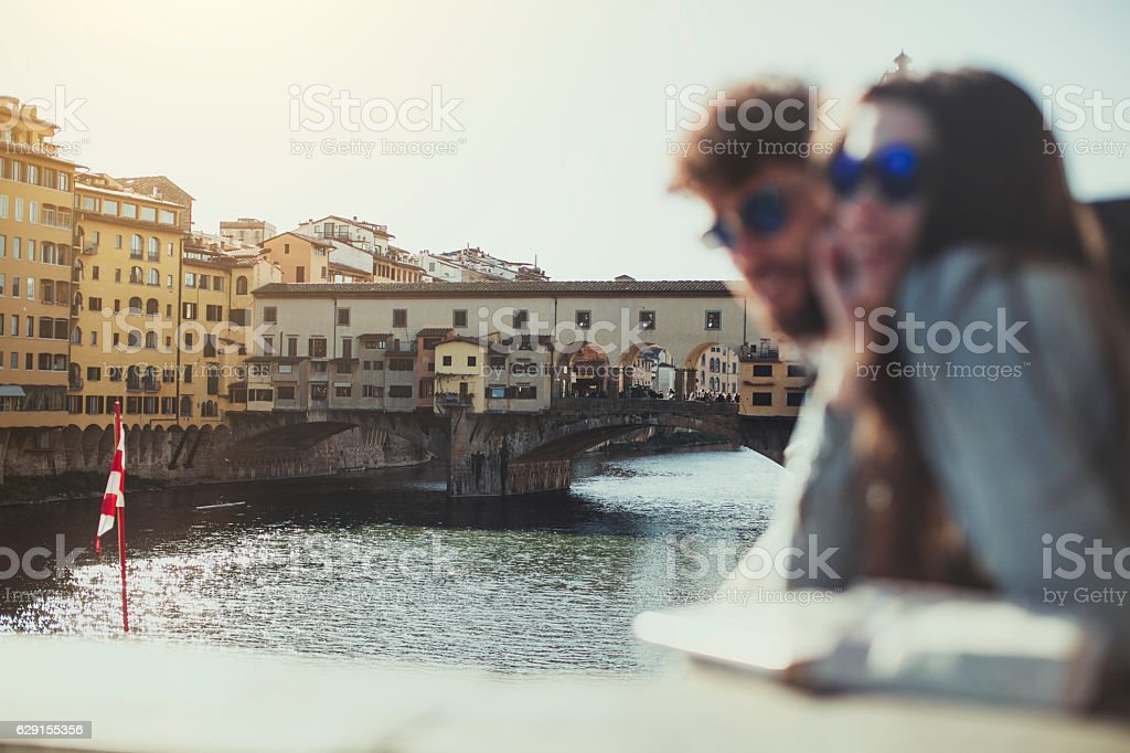 Couple by the Arno river at sunset, in Firenze stock photo
