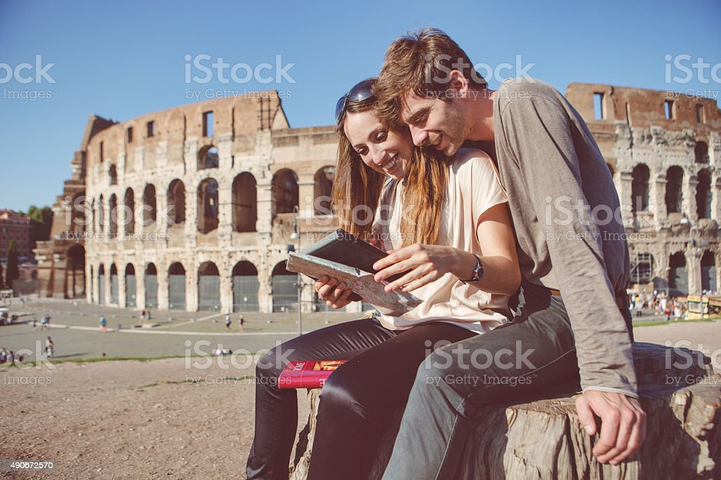 Couple by the Coliseum consulting tourist guide stock photo