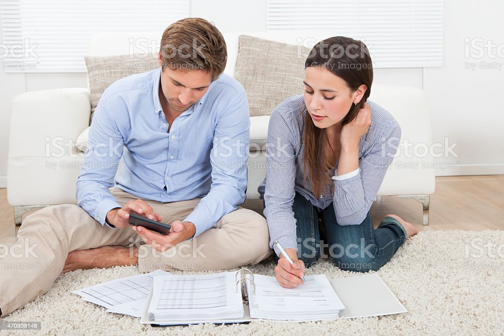 Couple Calculating Budget At Home stock photo