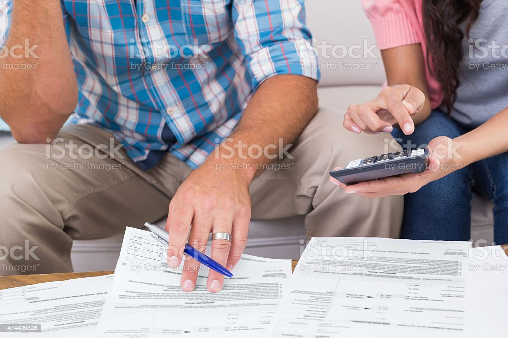 Couple calculating finances at home stock photo