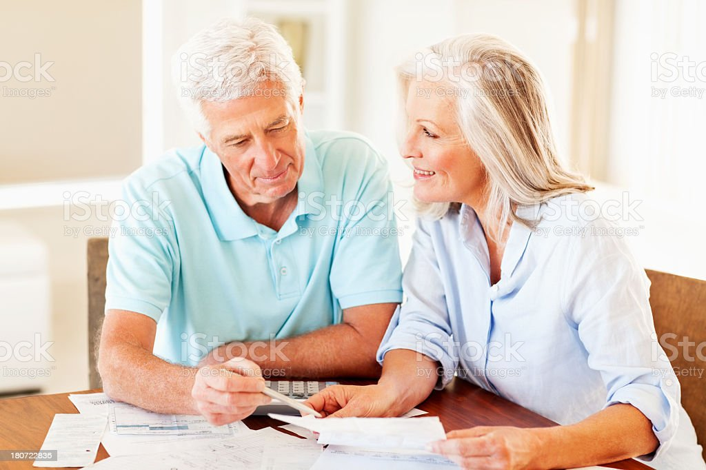 Senior couple calculating monthly expenses at home. Horizontal shot.