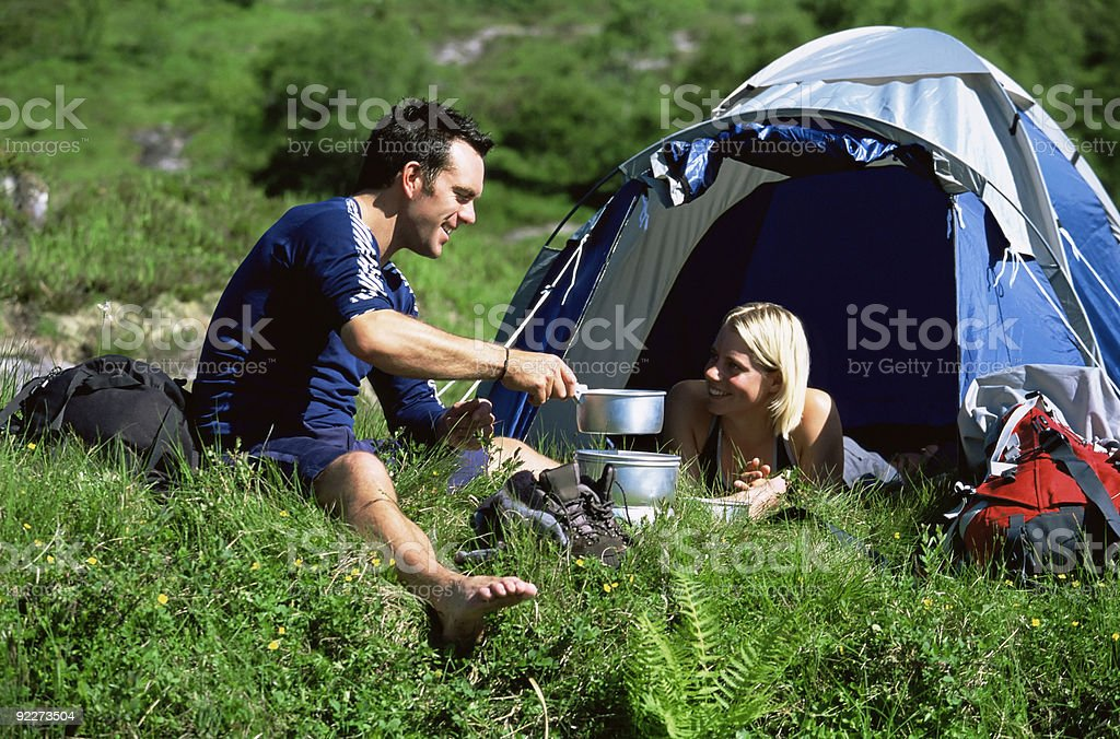 Couple camping outdoors and making food royalty-free stock photo