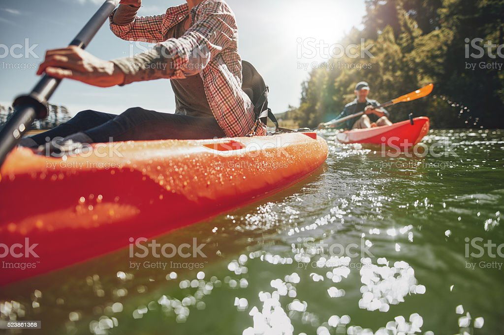 Couple canoeing in a lake on a summer day stock photo