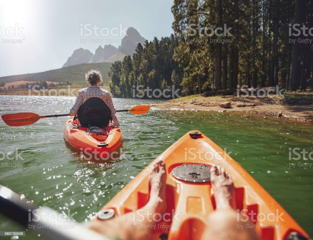 Couple canoeing in the lake on a summer day stock photo