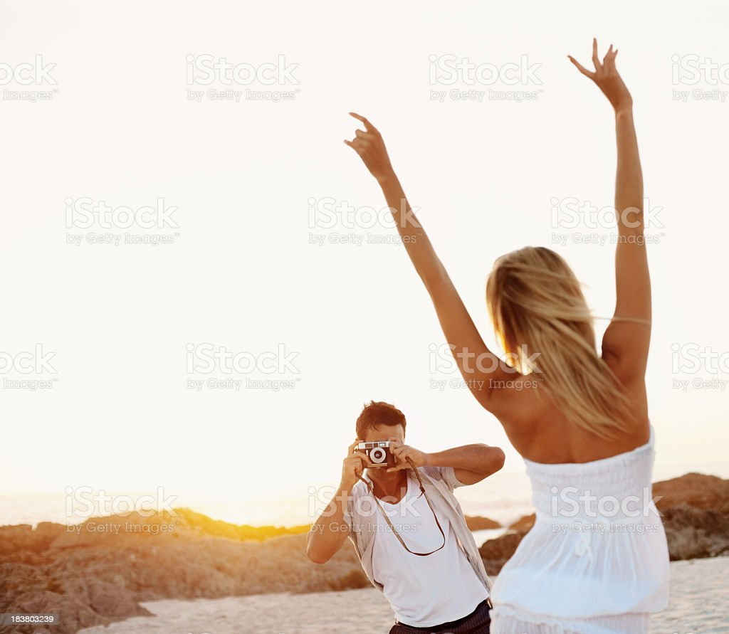 Couple capturing memories at beach royalty-free stock photo