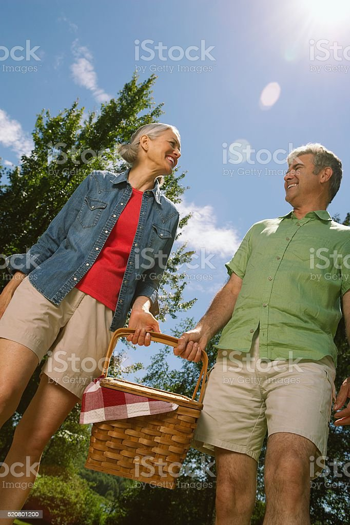 Couple carrying a picnic basket stock photo